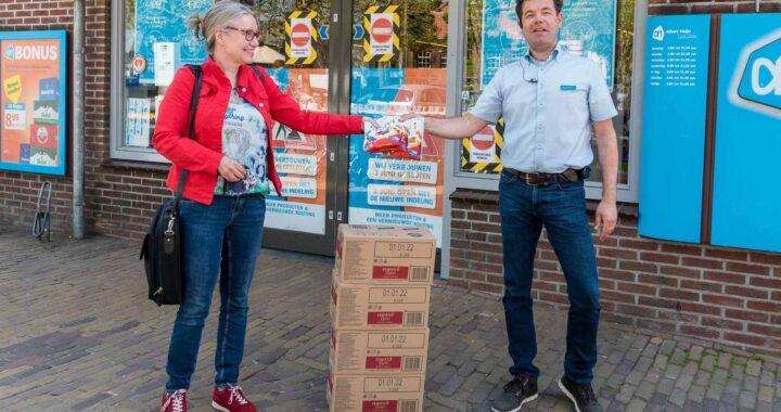 Martijn Steenman van AH Oude Dorp overhandigt zakjes Merci