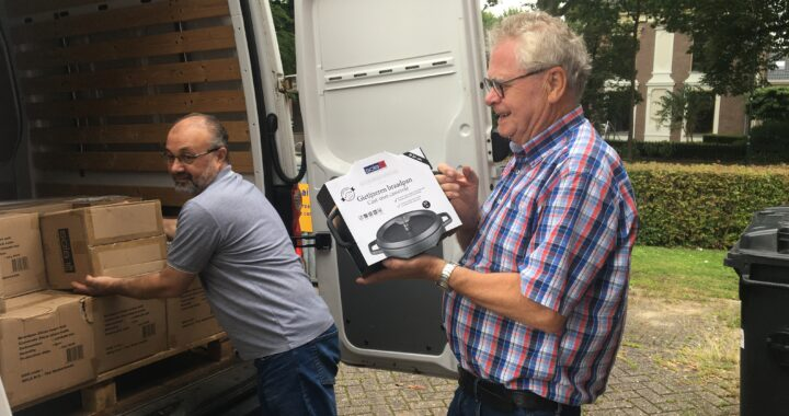 Vrijwilliger voedselbank neemt braadpan in ontvangst