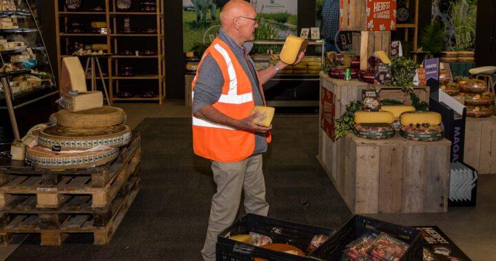 Vrijwilliger voedselbank vult kratten met kaas bij standhouder