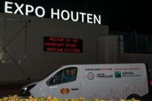 Koelbus voedselbank arriveert bij avond bij het beursgebouw